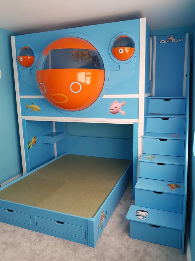 This is our Octonauts Pod Bed. Manufactured as a twin bed with a single bed up top and a double guest bed with two drawers underneath, and six drawers in the stairs. It was custom built with clear acrylic domes, and then sprayed orange with a viewing window. The bed was finished in blue.